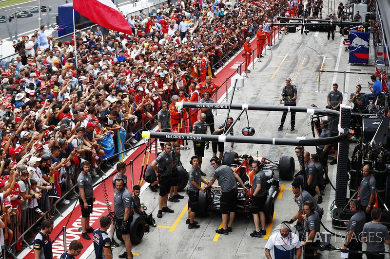 Fans watch the McLaren team at work