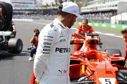 Third-qualifier Lewis Hamilton, Mercedes AMG F1, inspects the polesitting Sebastian Vettel Ferrari SF70H