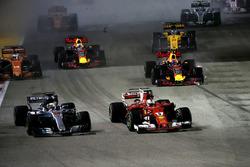 Старт гонки: лидирует Себастьян Феттель, Ferrari SF70H; на заднем плане поврежденный в столкновении с Кими Райкконеном Red Bull Racing RB13 Макса Ферстаппена