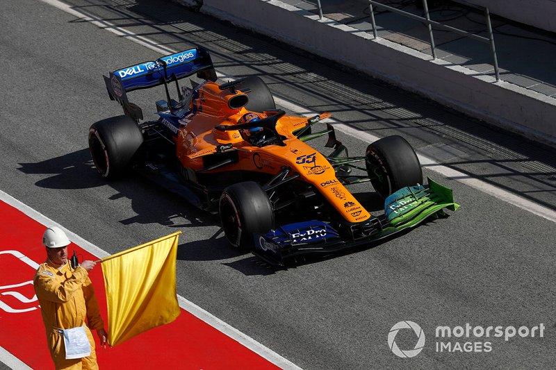 Carlos Sainz Jr., McLaren MCL34, accanto a un commissario con una bandiera gialla