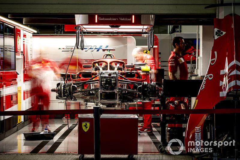 Engineers work on the car of Sebastian Vettel, Ferrari SF71H, in the garage