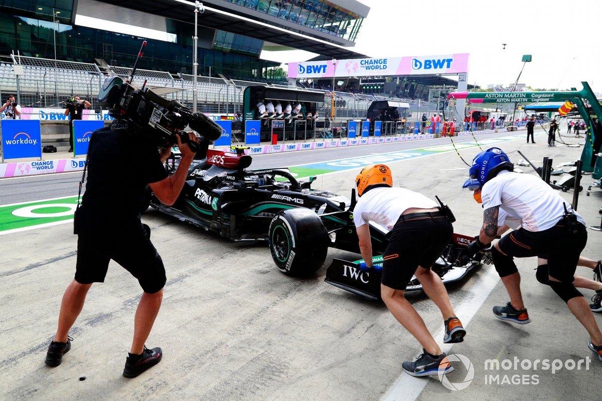McLaren pit crew members attempt to assist Valtteri Bottas, Mercedes W12, in the pitlane