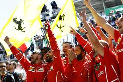 Ferrari team members celebrate at the podium