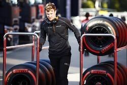 A McLaren mechanic wheels a trolley of Pirelli tyres