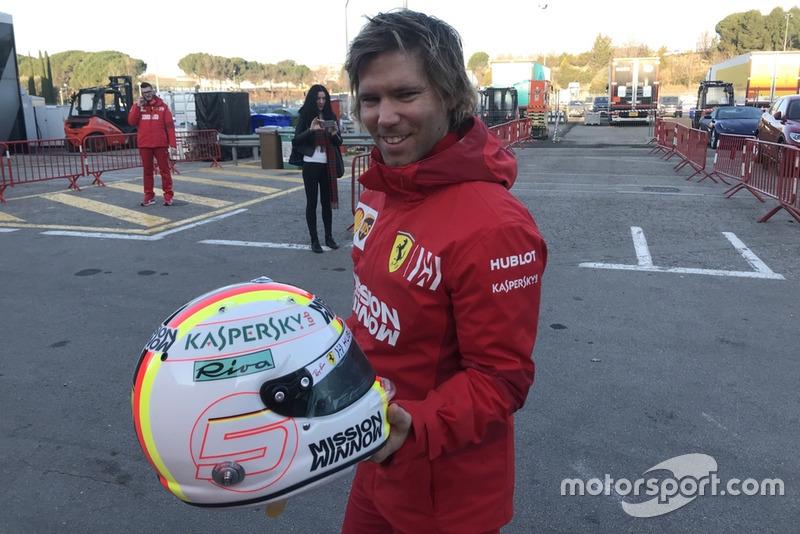 Antti Kontsas memegang helm Sebastian Vettel