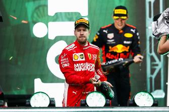 Sebastian Vettel, Ferrari, 2nd position, and Max Verstappen, Red Bull Racing, 1st position, spray Champagne on the podium