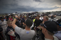 Competitors discuss what to do after a rain delay