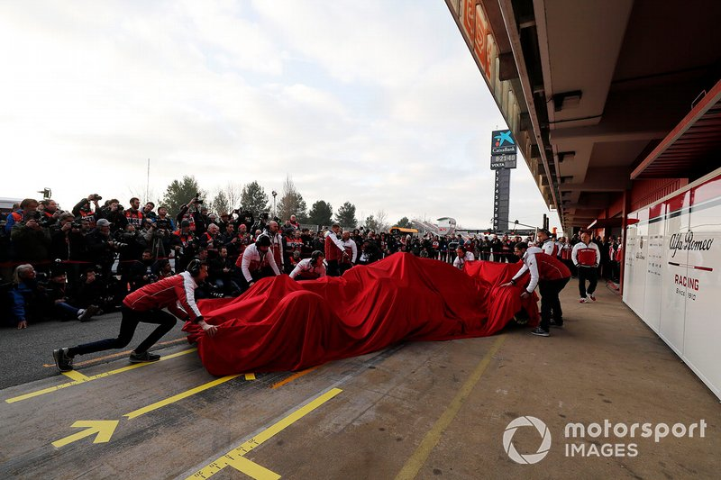 Alfa Romeo Racing mechanics with the Alfa Romeo Racing C38 under covers