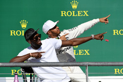 Race winner Lewis Hamilton, Mercedes AMG F1 celebrates on the podium with Usain Bolt
