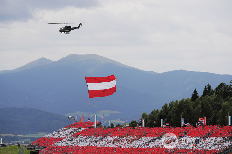 An Austrian flag is flown by helicopter over a grandstand of patriotic locals