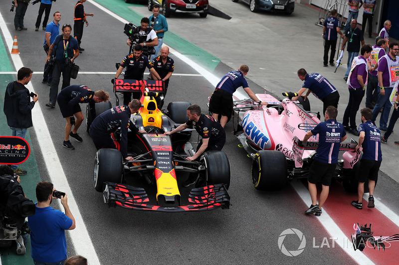 El coche de Max Verstappen, Red Bull Racing RB13 y Esteban Ocon, Sahara Force India VJM10 son empujados por la mecánica