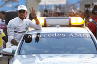 Lewis Hamilton, Mercedes AMG, celebrates pole from the window of a support car