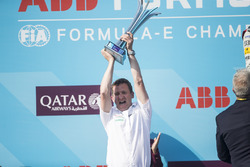 An Audi team member celebrates with the winning team trophy on the podium