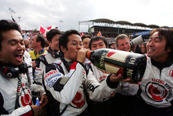 The Honda team celebrate with the Champagne