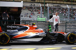 Kevin Magnussen, Haas F1 Team, climbs down from the pit wall as Stoffel Vandoorne, McLaren MCL32, passes