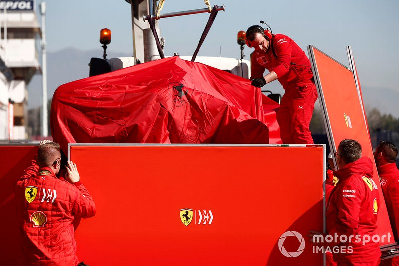 The car of Sebastian Vettel, Ferrari SF90 is recovered to the garage shielded by screens