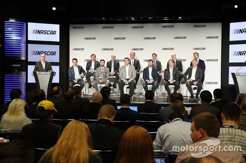 Ejecutivos y pilotos NASCAR se sientan en el escenario durante una conferencia de prensa que los cam