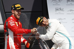 Sebastian Vettel, Ferrari, and Lewis Hamilton, Mercedes AMG F1, celebrate on the podium with champagne
