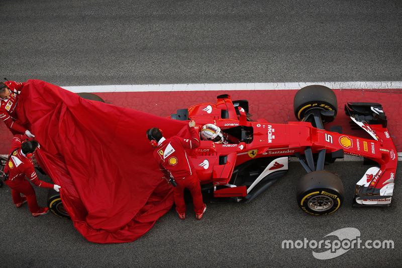Sebastian Vettel, Ferrari SF70H, kembali ke pit saat mekanik menutup bagian belakang mobil
