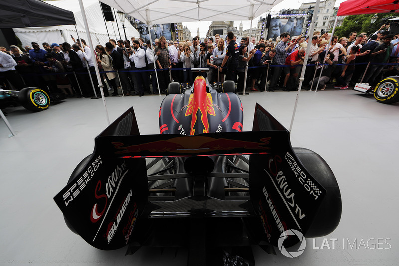 Fans inspect and photograph the Red Bull Racing RB13 on the Red Bull Racing stand