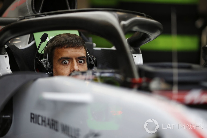 A Haas mechanic sits in the cockpit of a Haas F1 Team VF-18