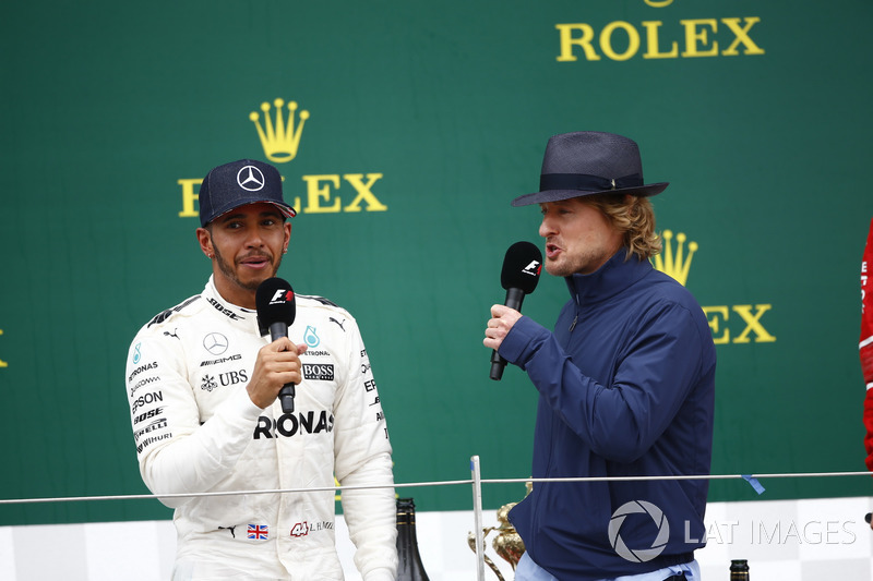 Actor Owen Wilson interviews Race winner Lewis Hamilton, Mercedes AMG F1, on the podium