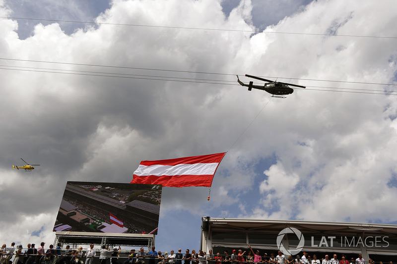 Гелікоптер летить із прапором Австрії над стартовою решіткою