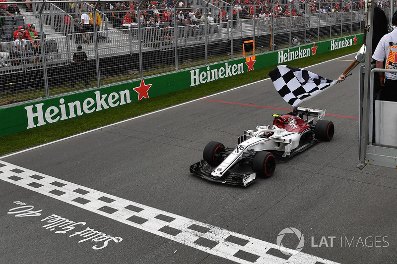 Charles Leclerc, Sauber C37 takes the chequered flag waved by Winnnie Harlow (CDN)