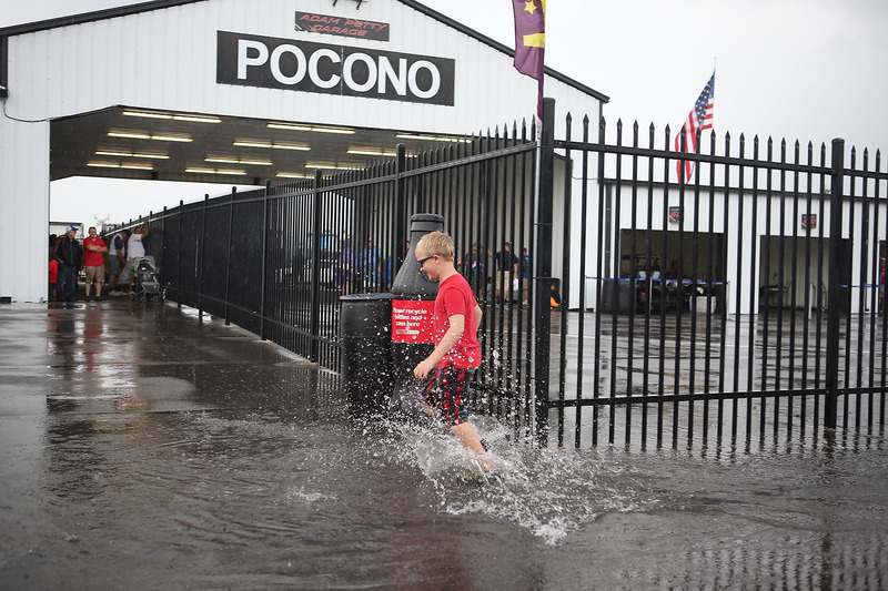 Un giovane tifoso corre tra le pozzanghere nel paddock del Pocono Raceway