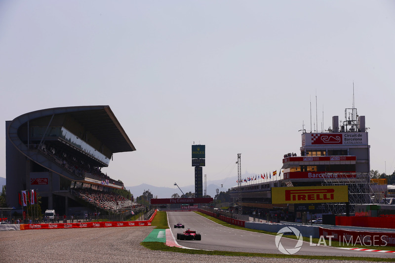 A Ferrari follows a Force India onto the pit straight