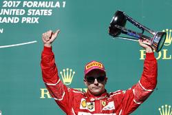 Third place Kimi Raikkonen, Ferrari, lifts his trophy