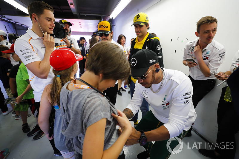 Lewis Hamilton, Mercedes AMG F1, signs a grid kid's short, as Carlos Sainz Jr., Renault Sport F1 Team, Fernando Alonso, McLaren and Stoffel Vandoorne, McLaren, look on