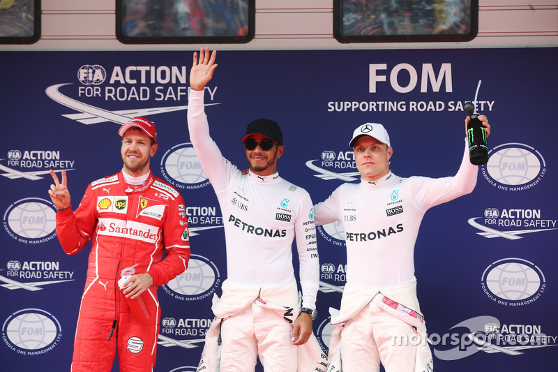 Lewis Hamilton, Mercedes AMG, celebrates taking pole position alongside Sebastian Vettel, Ferrari and Valtteri Bottas, Mercedes AMG