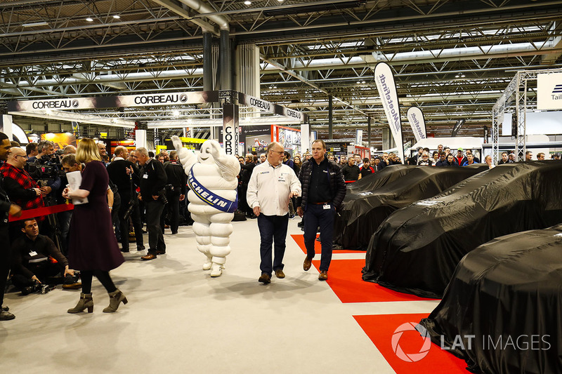 A Michelin man walks past WRC cars under covers