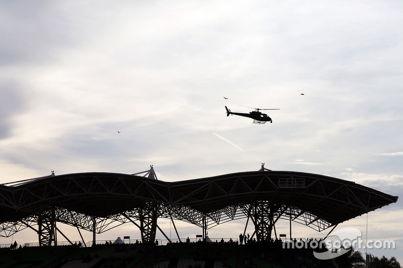 A helicopter flies over a grandstand