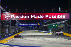 Carlos Sainz Jr., Scuderia Toro Rosso STR12, passes as Esteban Ocon, Sahara Force India F1 VJM10, emerges from the pits