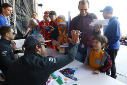 Fernando Alonso, McLaren, give a high-five to a young fan, as Stoffel Vandoorne, McLaren, signs autographs