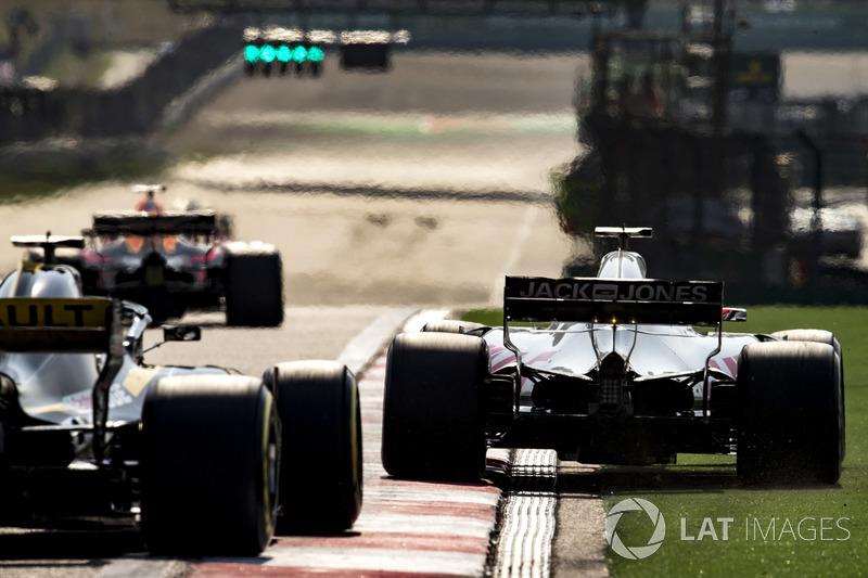 Romain Grosjean, Haas F1 Team VF-18 Ferrari, runs wide ahead of Nico Hulkenberg, Renault Sport F1 Te