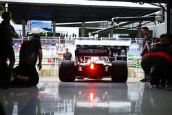 Los mecánicos de Haas ven a Kevin Magnussen, Haas F1 Team VF-18, salir del garaje del equipo