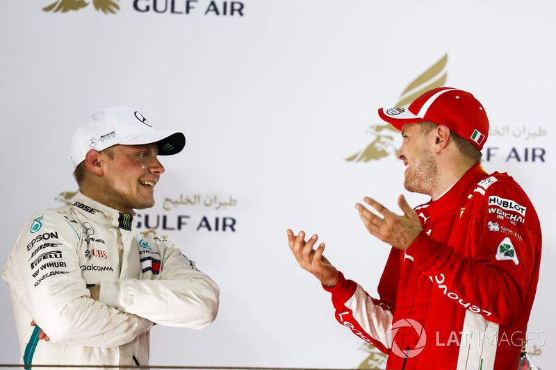 Valtteri Bottas, Mercedes AMG F1, 2nd position, and Sebastian Vettel, Ferrari, 1st position, talk on