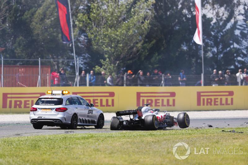 Un coche oficial se detiene al lado del monoplaza accidentado de Romain Grosjean Haas F1 Team VF-18