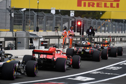 Cars queue at the red light in pit lane
