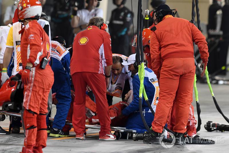 Un mécanicien Ferrari pris en charge par les services médicaux après avoir été percuté par Kimi Raikkonen, Ferrari SF71H pendant un arrêt au stand