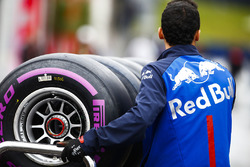 Un membro del team Toro Rosso attraversa il paddock con degli pneumatici Pirelli