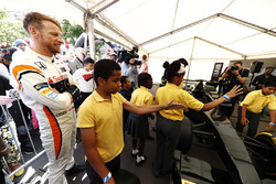 Jenson Button, McLaren, cheers on a team of school children during a pit stop challenge