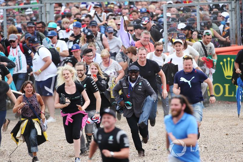Los fans se apresuran al podio para celebrar