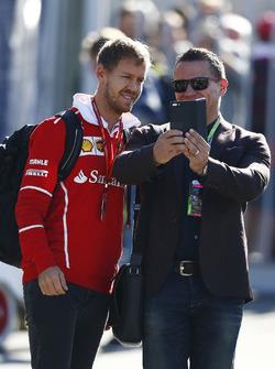 Sebastian Vettel, Ferrari, takes a picture with a fan
