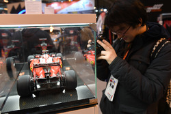 A fan takes a picture of an Amalgam Ferrari model