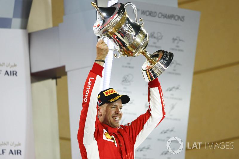 Sebastian Vettel, Ferrari, mengangkat trofi di podium