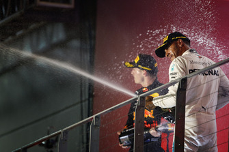 Lewis Hamilton, Mercedes AMG F1, and Max Verstappen, Red Bull Racing, celebrate on the podium with champagne